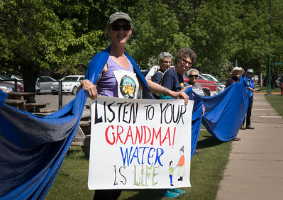"""Image shows woman holding a sign that says """"Listen to your grandma! Water is life."""""""