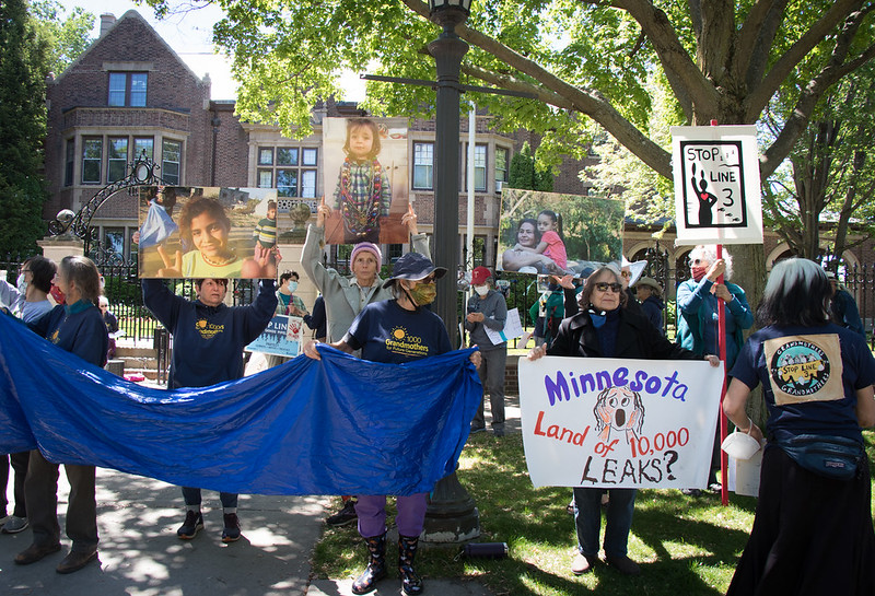 Image shows members of 1000 Grandmothers and Lakota and Ojibwe women holding signs outside of the Governor's mansion.